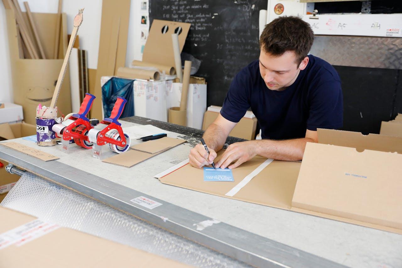 Modulor Logistik am Moritzplatz: Tim unterschreibt die Dankeskarte an die Modulor Kunden, die aktuell allen Paketen beigelegt ist
