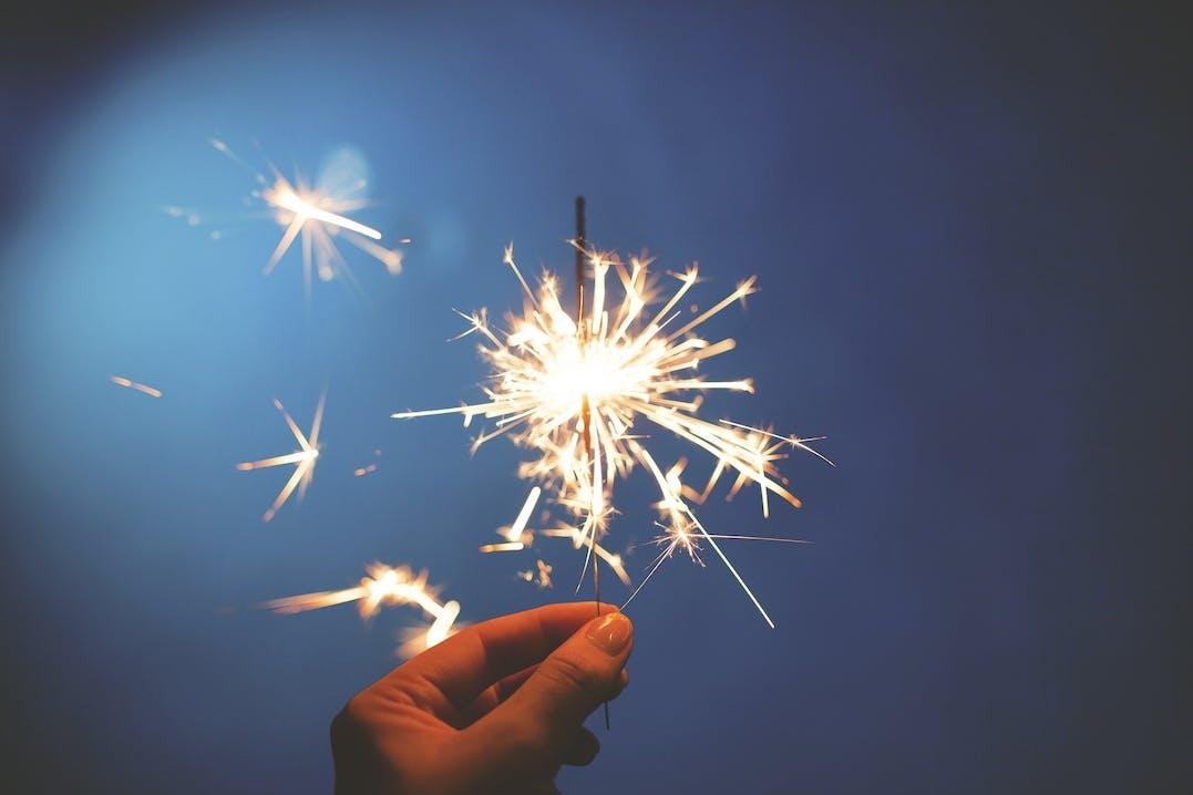 Eine Hand hält eine Wunderkerze, die am leuchten ist und Funken sprüht.
