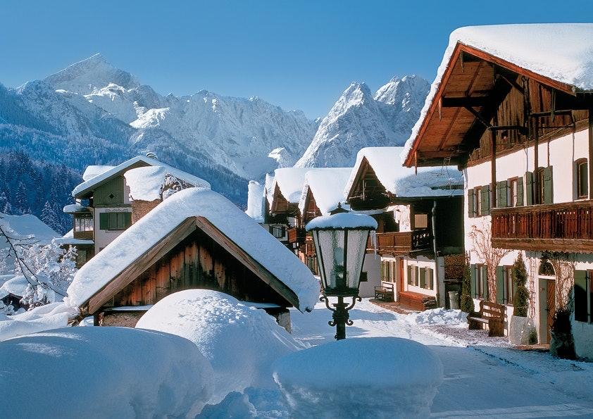 Holzhütten in Berglandschaft und mit viel Schnee bedeckt.