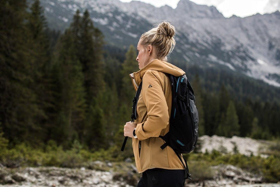 Frau beim Wandern in gelber OCK Jacke