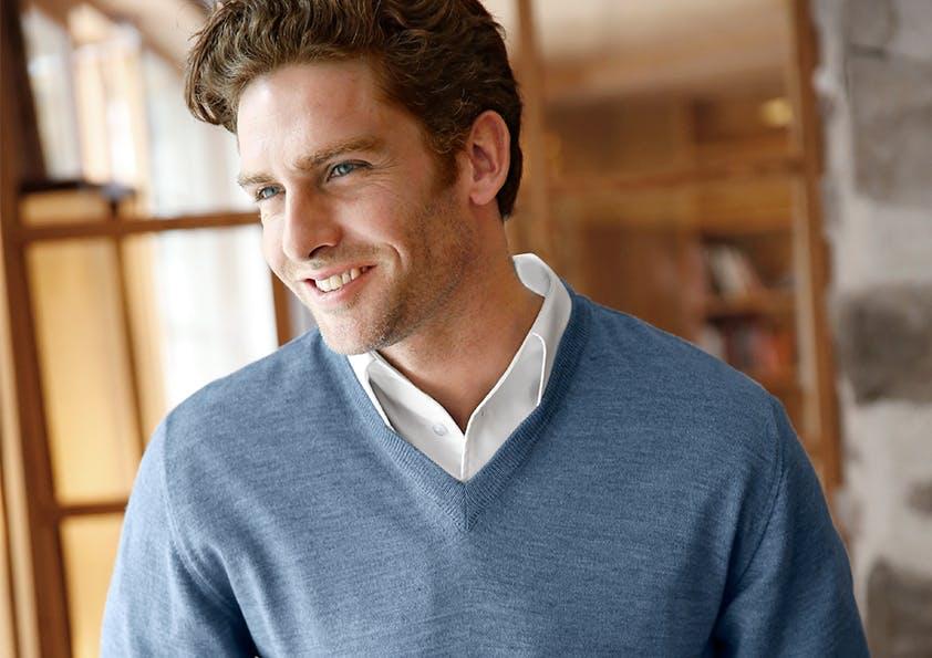 Mann mit weißem Hemd und blauem V-Pullover lächelt.