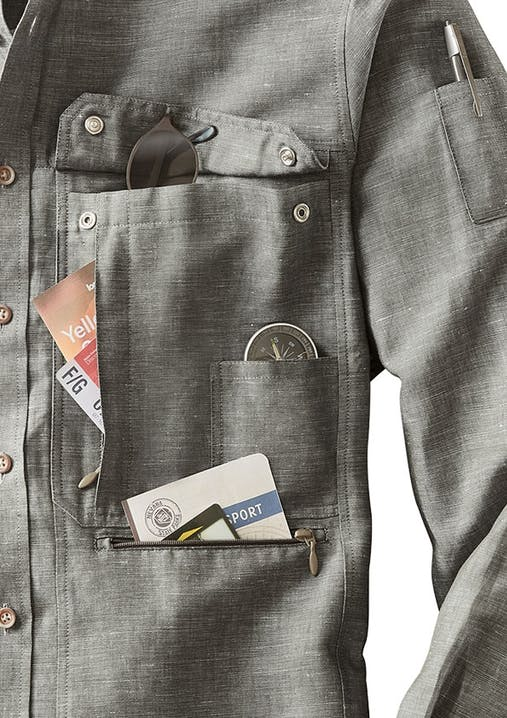 Hemd mit aufgeknöpfter Brusttasche. Darin streck eine Sonnenbrille, Papieren und ein Kompass. Am Ärmel ist eine Tasche mit einem Stift darin.