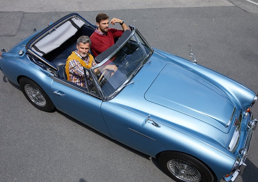 Zwei Männer sitzen in blauen Oldtimer-Cabrio