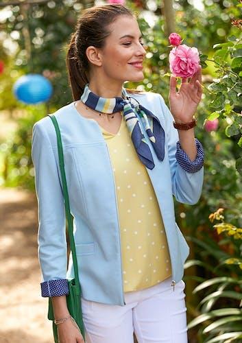 Frau riecht an Blume_gelbe Bluse mit weißen Pünktchen und Blazer in Hellbl