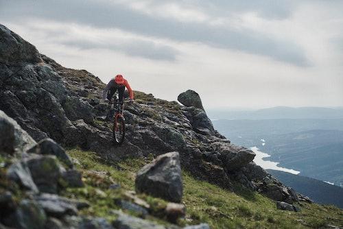 Uomo che scende da montagna con mountainbike
