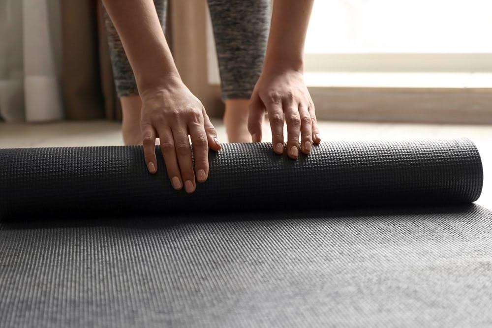 Frau rollt Yogamatte aus