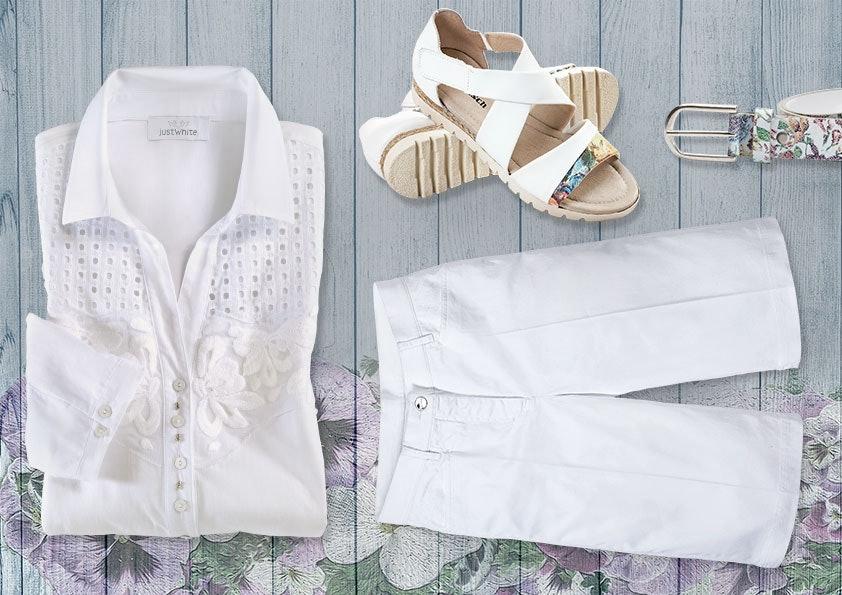 Weiße Bluse, weiße Hose, Sandalen und Gürtel auf einem grauen Holzhintergrund.