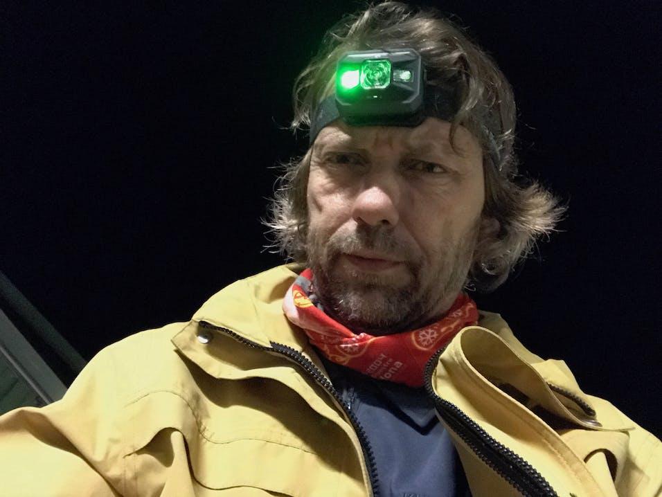 Mann mit Dreitagebart und Stirnlampe schaut in das Bild und trägt ein rotes Halstuch und eine gelbe Jacke.