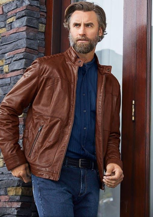 Mann mit Bart steht vor einer Haustür und trägt ein blaues Hemd, Jeans und eine braune Lederjacke.