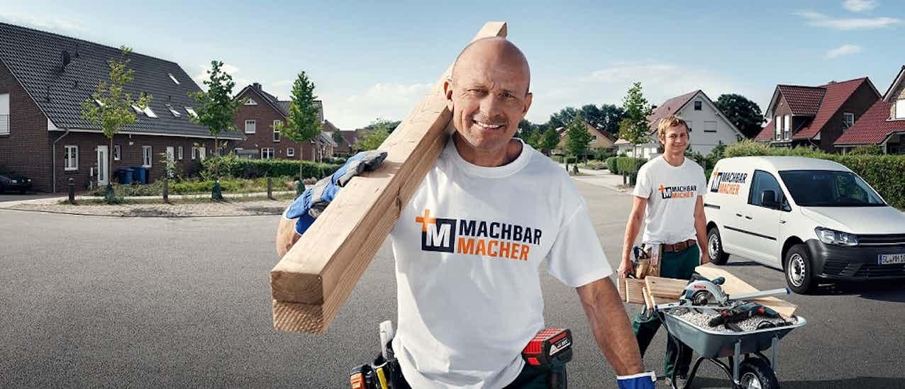 Handwerker/MachbarMacher, der gerade zu einer Baustelle mit Holz auf der Schulter geht