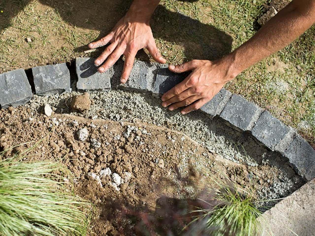 Gartenlandschaftsbauer verlegt Rasenkanten für eine Beetumrandung