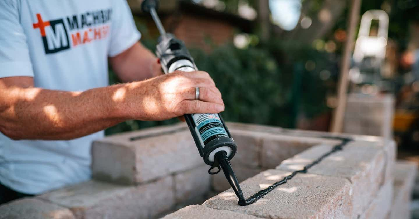 Mauerer baut eine Mauer im Garten für eine Outdoor-Küche