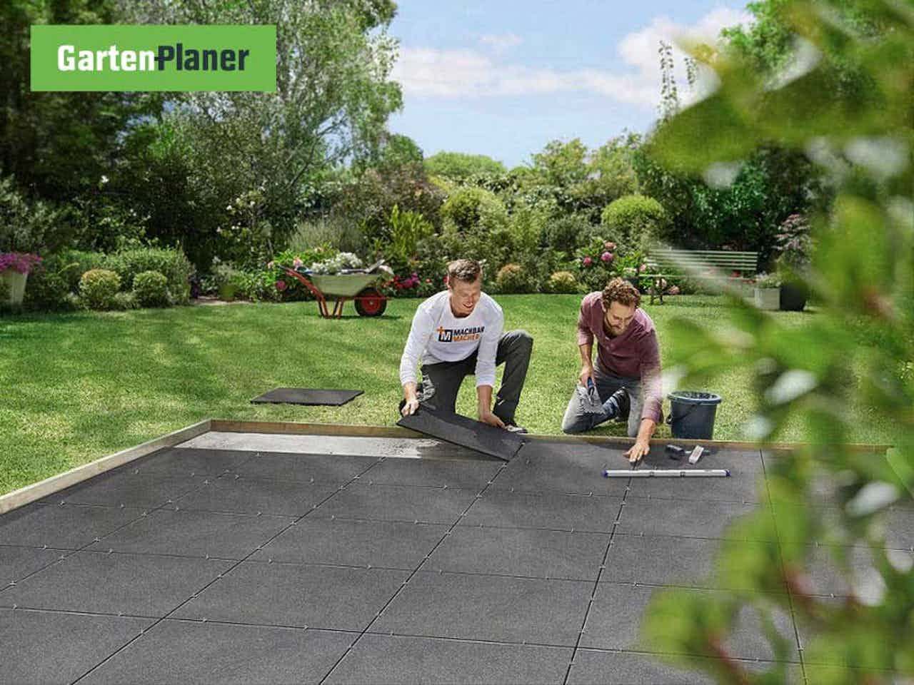 Gartenlandschaftsbauer verlegt Terrassenplatten für eine neue Terrasse im Garten