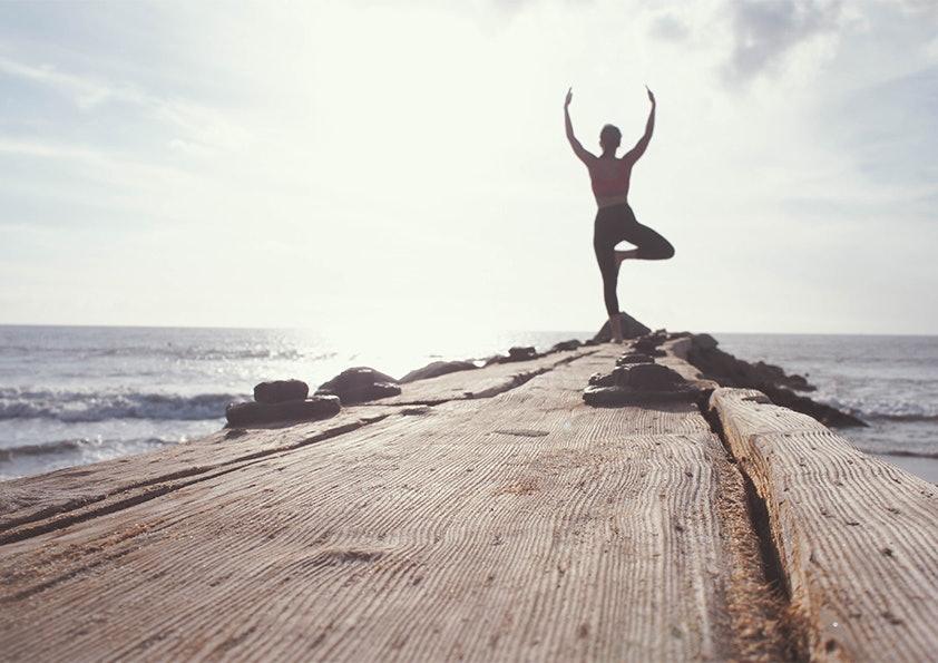 Frau auf einem Holzsteg über dem Meer macht eine Yoga-Übung.