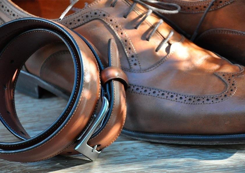 Brauner Gürtel mit silberner Schnalle lehnt an einem braunen Schuh mit eingestanzten Löchern und Schnürsenkeln.