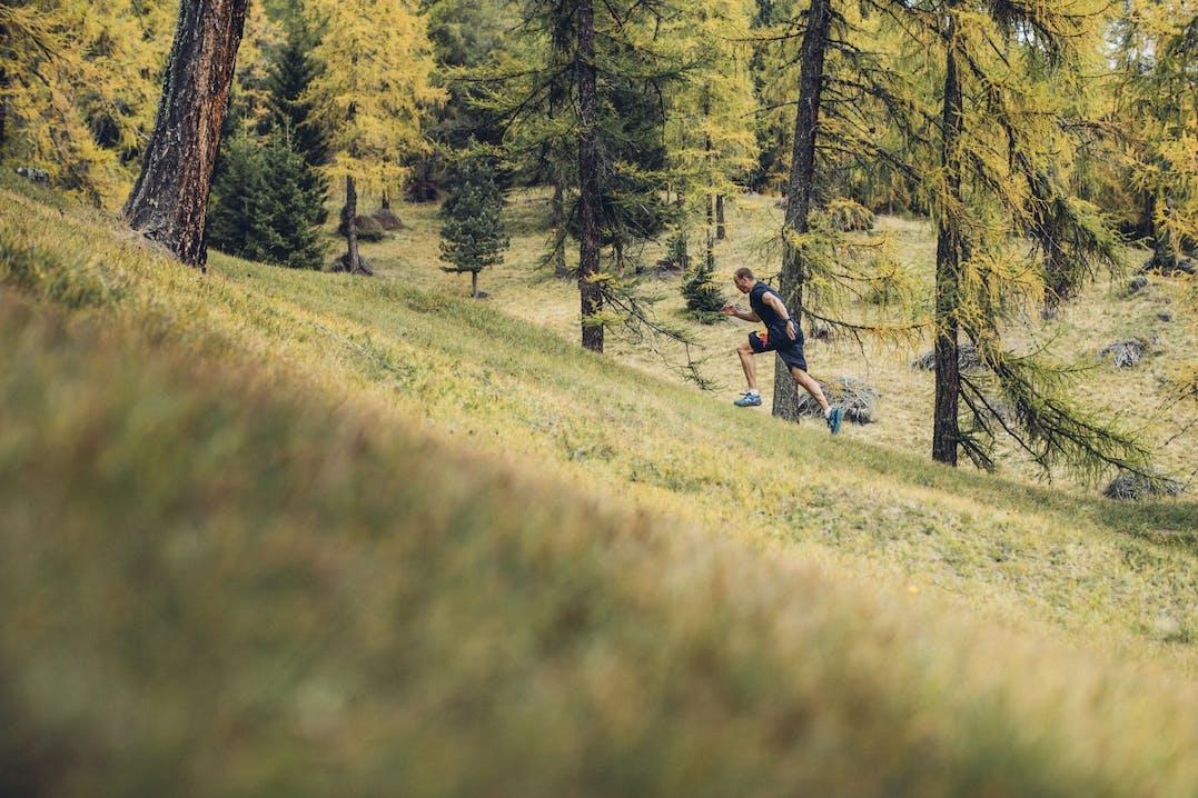 Foto di uomo che corre in ambiente boschivo