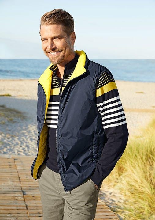 Ein Mann mit blau-gelber Weste steht lächelnd im Vordergrund. Im Hintergrund sieht man einen Sandstrand mit blauem Wasser.
