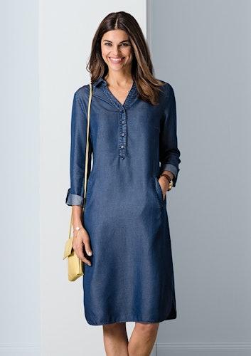 Lächelnde Frau mit blauem Jeanskleid und kleiner gelber Tasche.