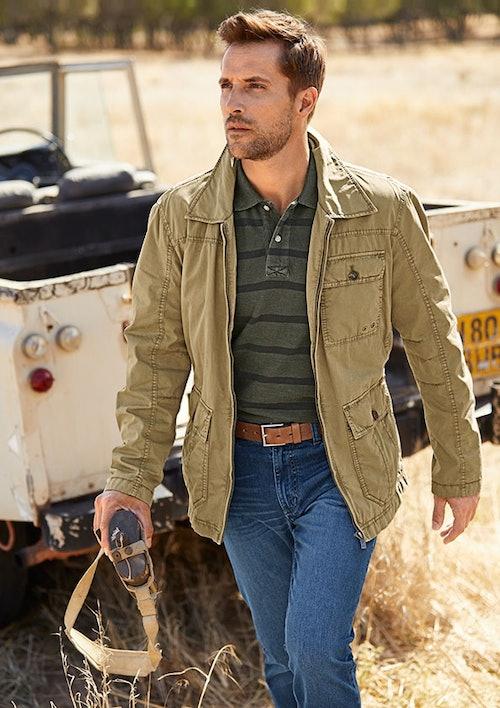 Mann in braun-grüner Jacke mit vielen Taschen, grünem Polo, Jeans und mit braunem Gürtel. Er hält eine Trinkflasche mit Gurt in der Hand. Im Hintergrund ein rustikaler Geländewagen und trockenes Gras.