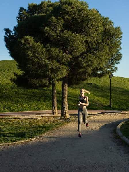 Vaaleahiuksinen nainen, jolla on yllään musta lyhyt toppi, pitkät harmaat leggingsit ja punaiset lenkkitossut, lenkkeilee puiston halki.