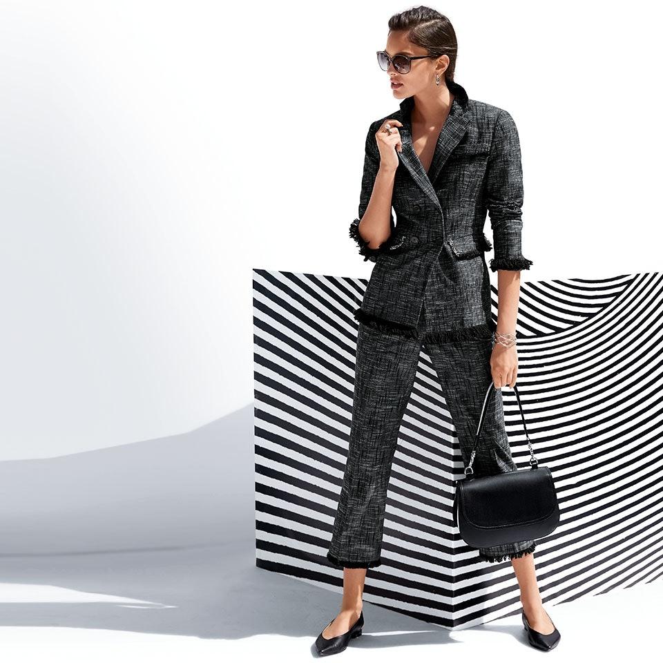 Frau mit Sonnenbrille in dunkelgrauem Zweiteiler bestehend aus Blazer und Hose.