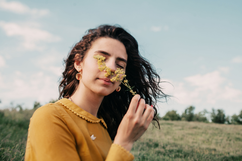A healthy woman smelling a wild flower in an open field