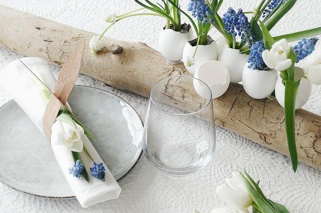Stillleben mit österlicher Deko bestehend aus Eierschalen, die mit lieblichen Blumen gefüllt sind.
