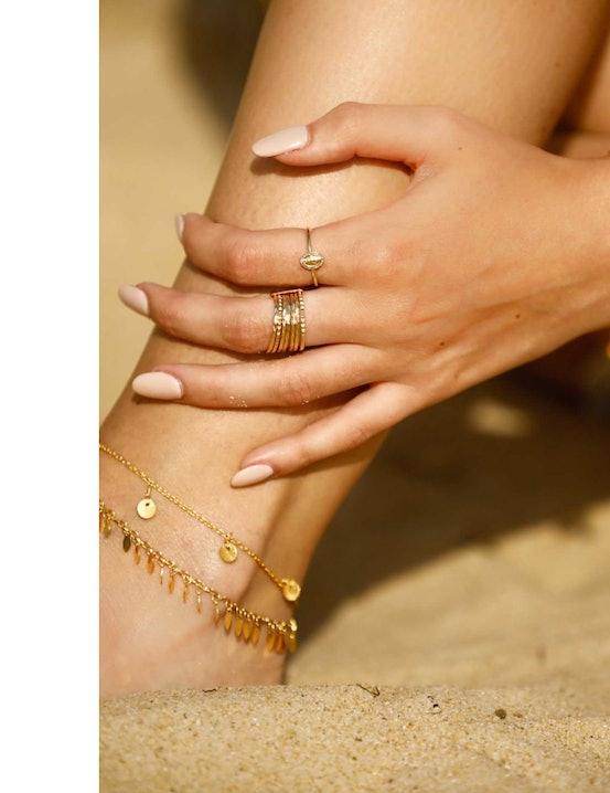le bracelet 3 rangs madone pastel CHARLOTTE aux couleurs de glaces à l'eau. Il est composé de trois rangs : un premier paré de médaillons en métal martelé, d'une chaine aux perles acidulées et enfin, d'une chêne ornée d'un pompon et d'une médaille à l'effigie d'une madone protectrice.