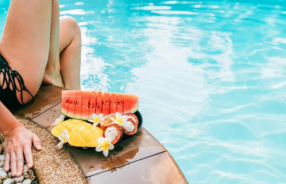 Frau isst Früchte am Pool