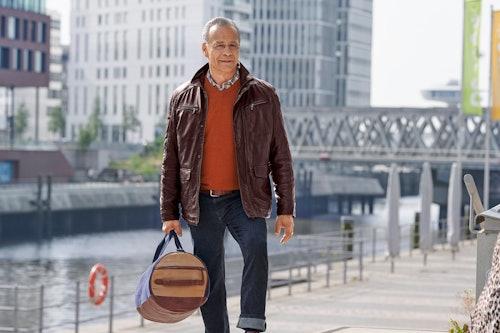 Mann mit dunkelbrauner Lederjacke, orangenem Pulli, Jeans und einer Reisetasche geht auf einem Hafensteg.