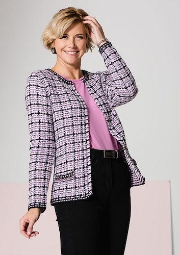 Lächelnde Frau mit rosa Shirt, dunkler Hose und pink-schwarz kariertem Blazer.