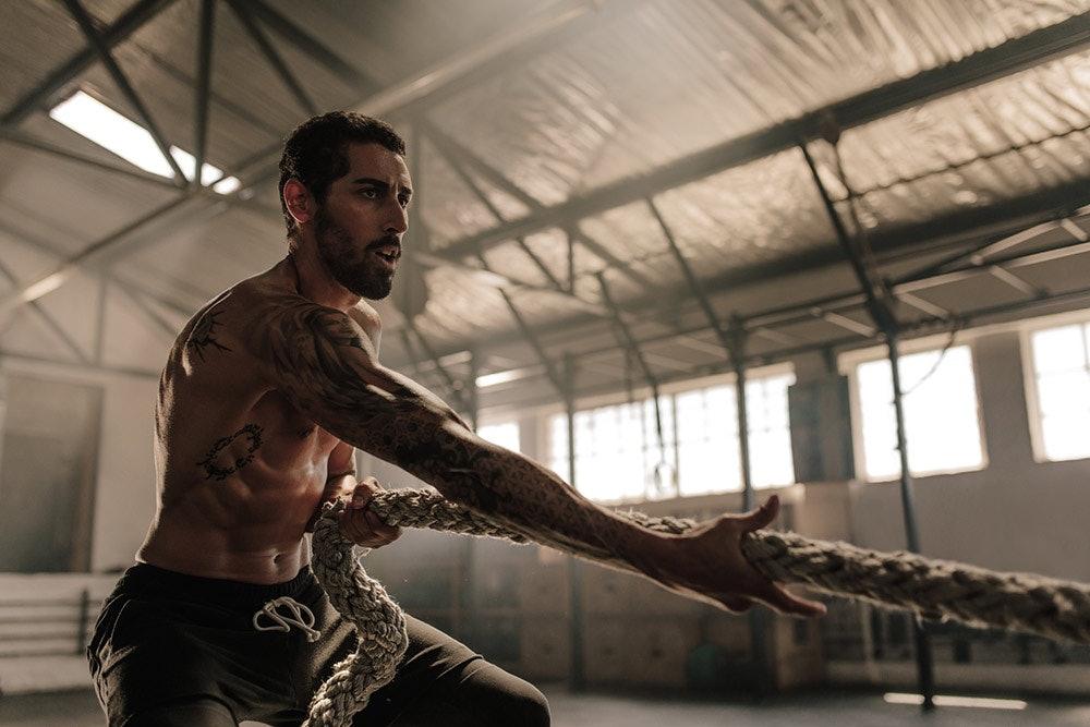 Sportlicher Mann beim Rope Workout Crossfit