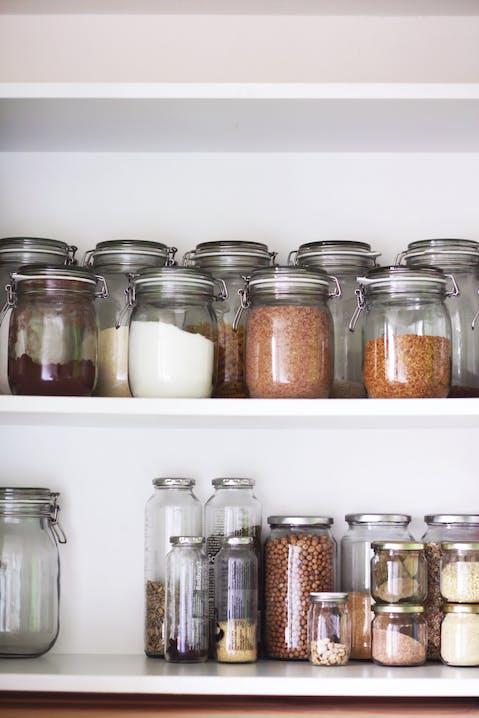Aufbewahrungsgläser mit Trockenzutaten stehen in Reihe in einem Küchenschrank