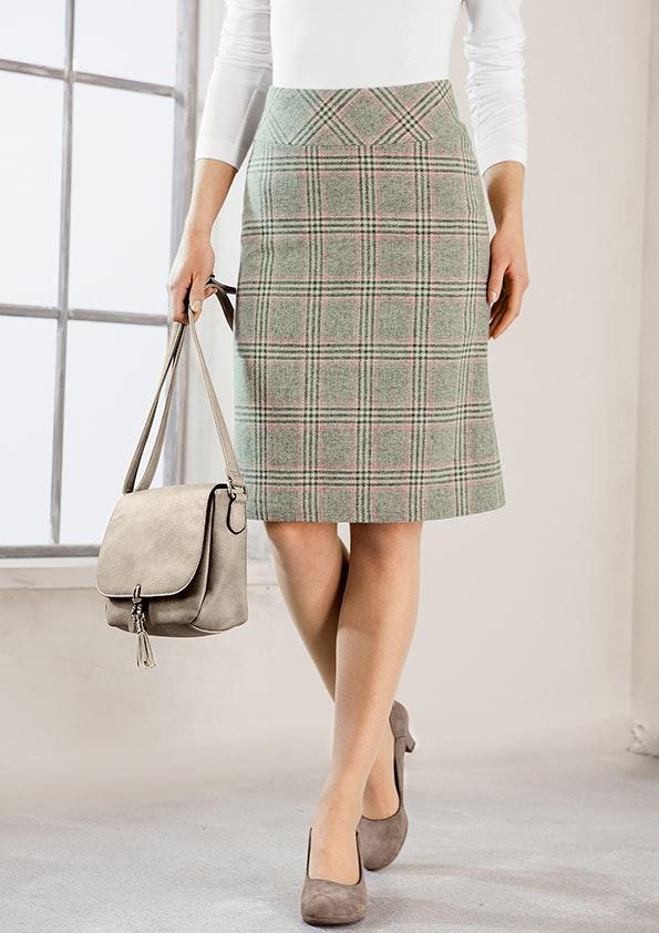 Anschnitt einer Frau zeigt einen grauen Karorock und beige Pumps. In der Hand hält die frau eine kleine Tasche.