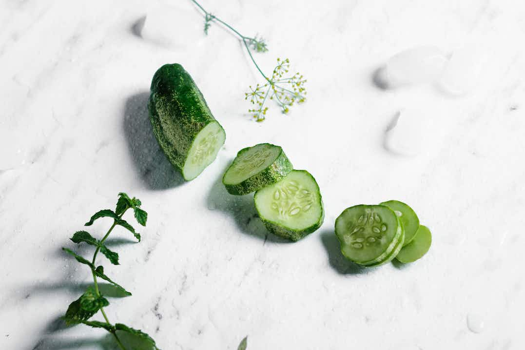Sliced and chilled cucumber sitting on a white marble surface with wild flower stems and ice cubes surrounding it