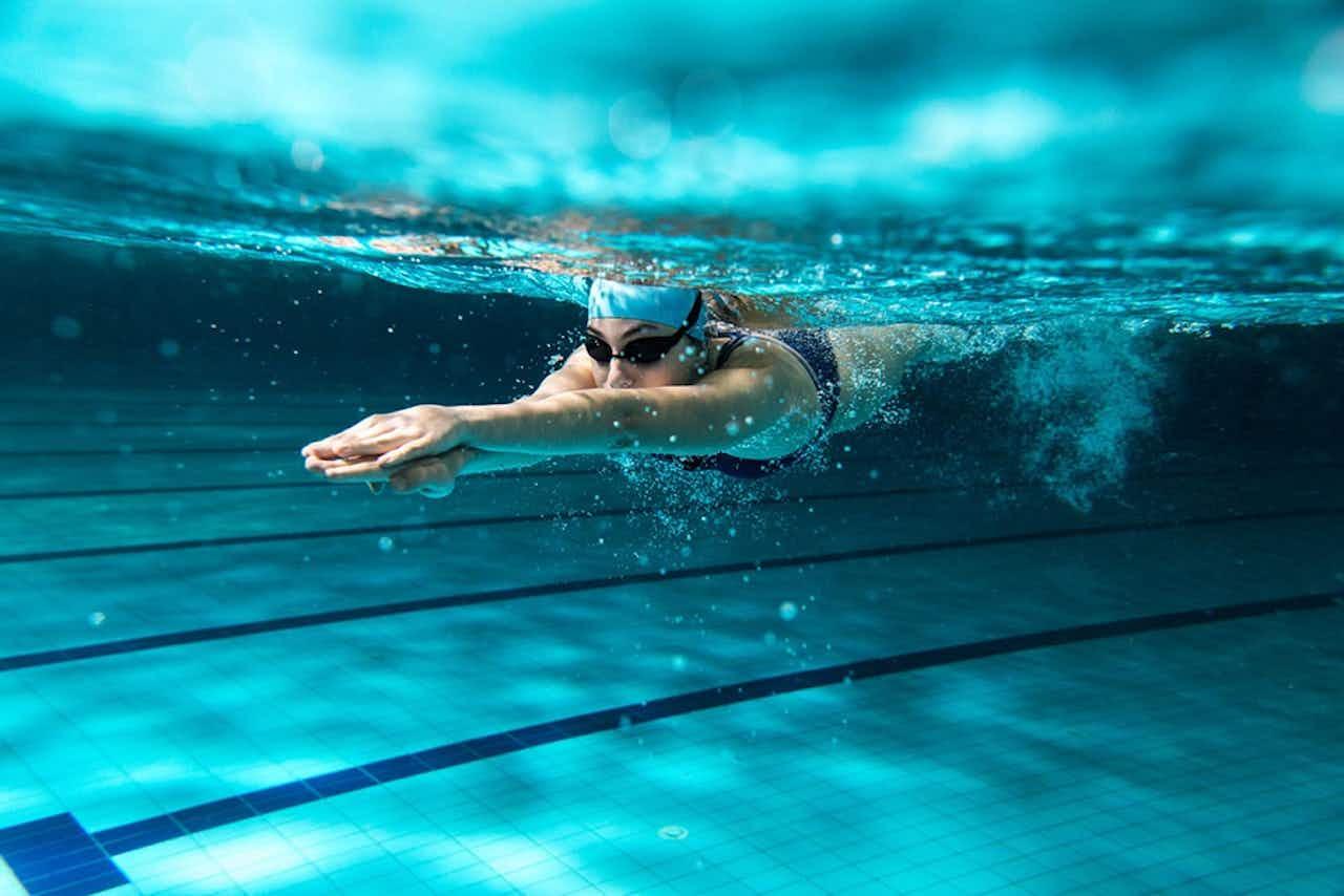 Schwimmerin unter Wasser im Pool