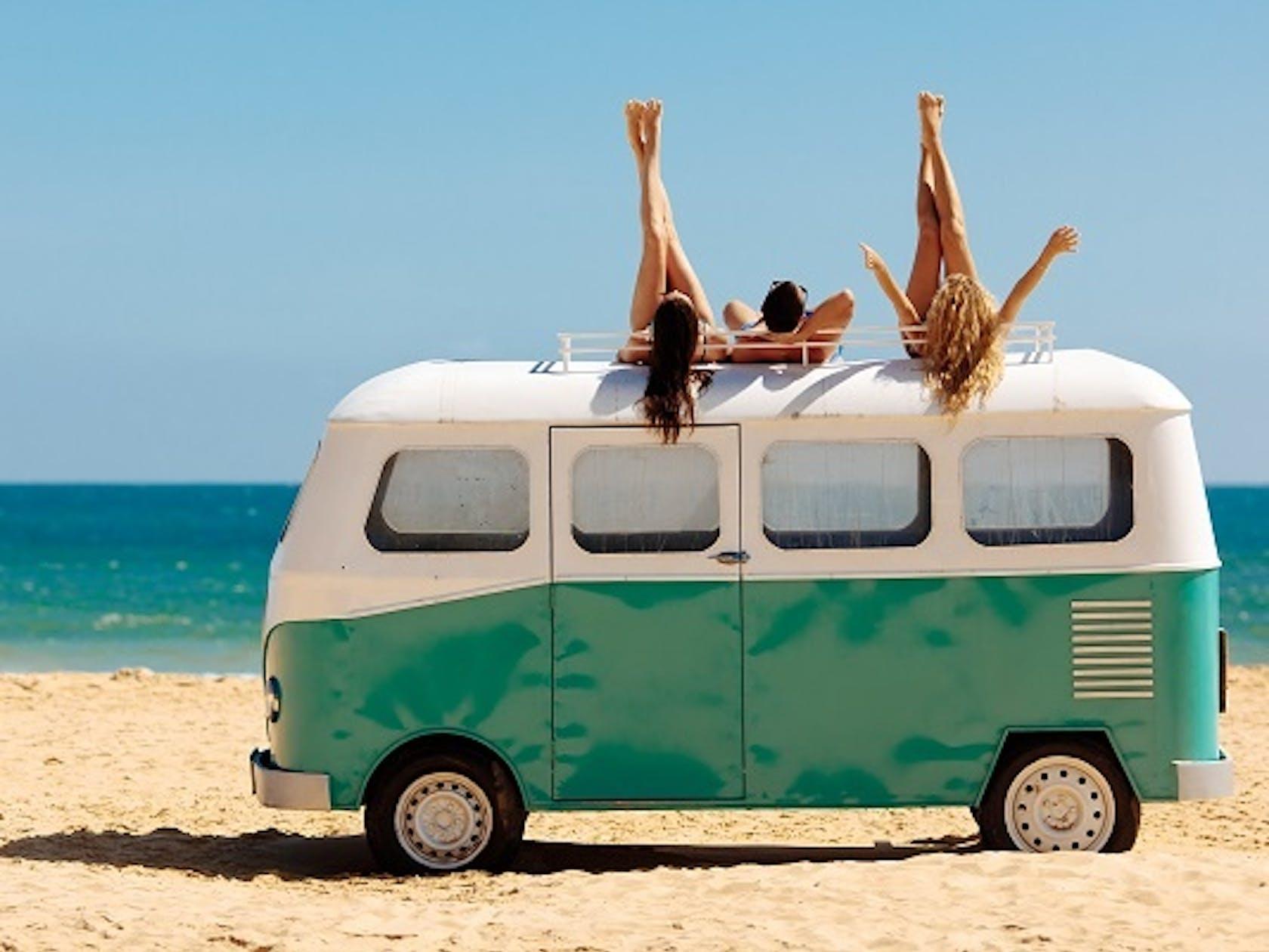 Jugendliche liegen auf Camper-Bus im Sommer am Strand und strecken Beine in die Luft