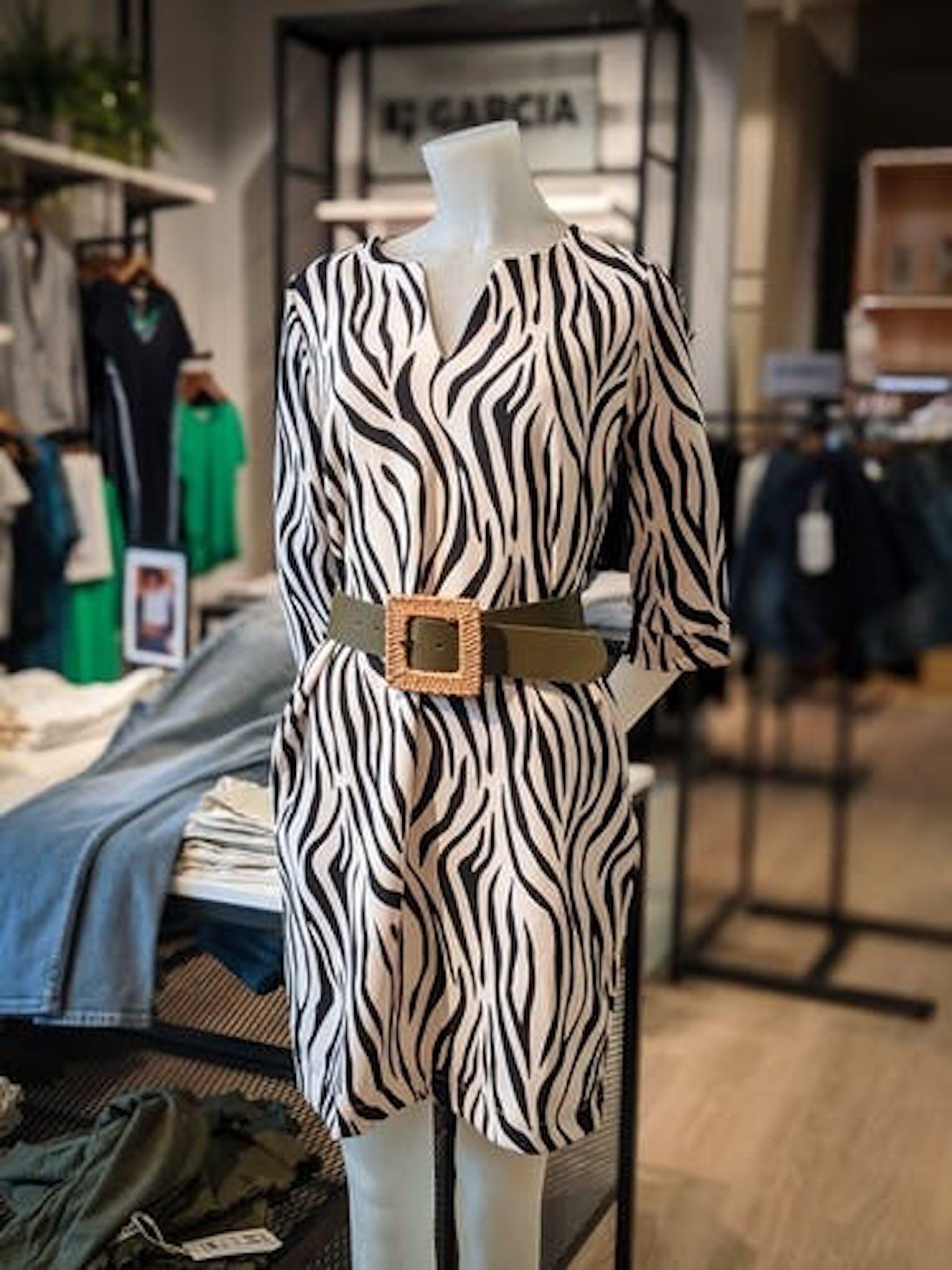 Schaufensterpuppe trägt Kurzes Kleid mit Zebra-Print und Taillengürtel in oliv