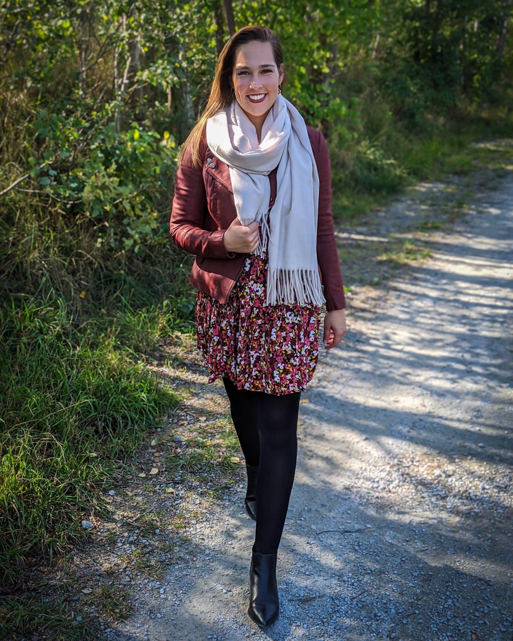 junge Frau in modischem Outfit geht einen Waldweg entlang