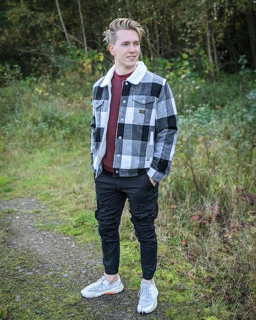Junger Mann zeigt Mode mit Karomuster