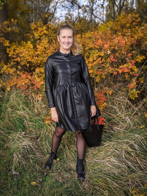 junge Frau im schwarzen Kleid aus Lederimitat von Only