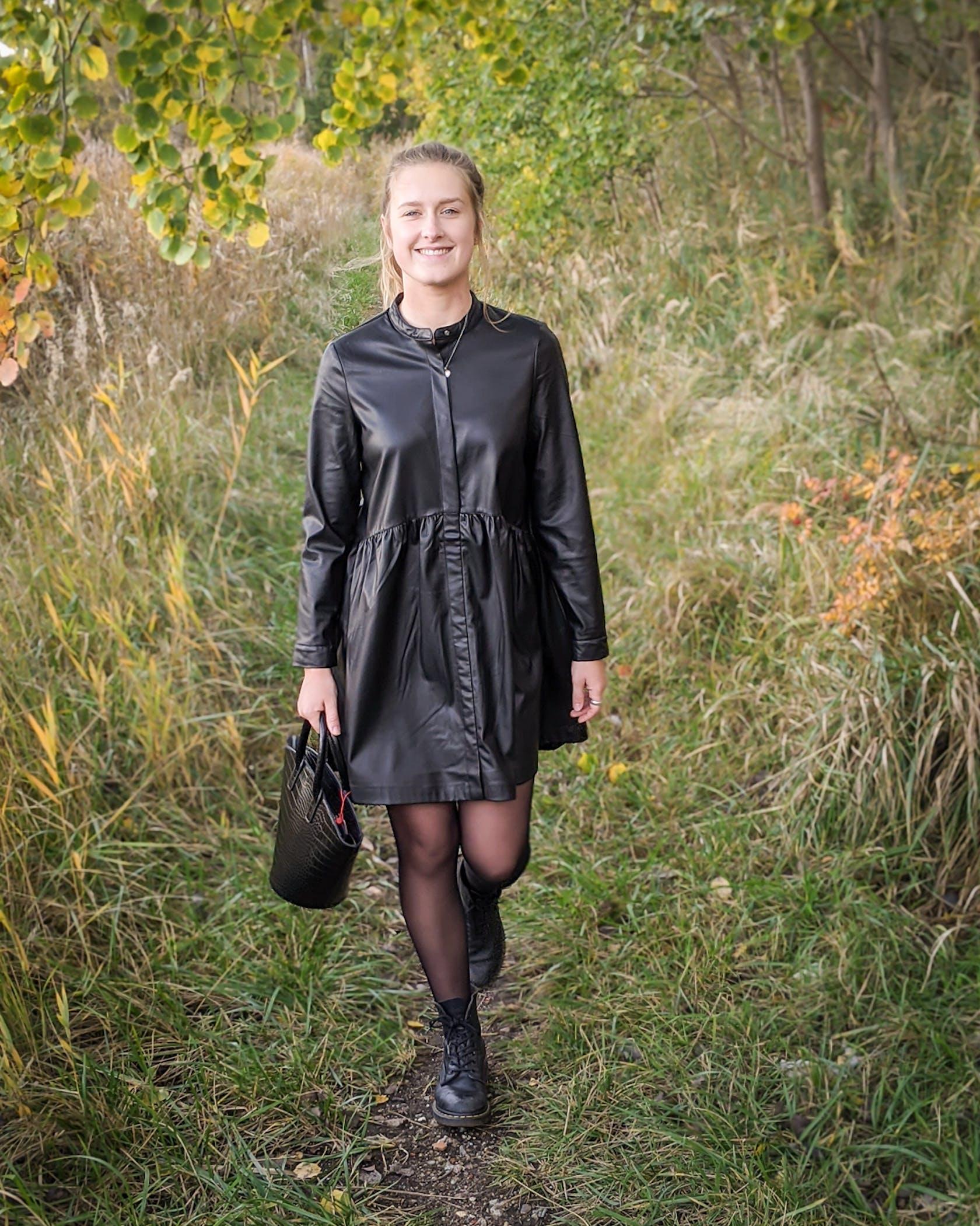 june Frau in schwarzem Lederimitatkleid läuft einen Waldweg entlang