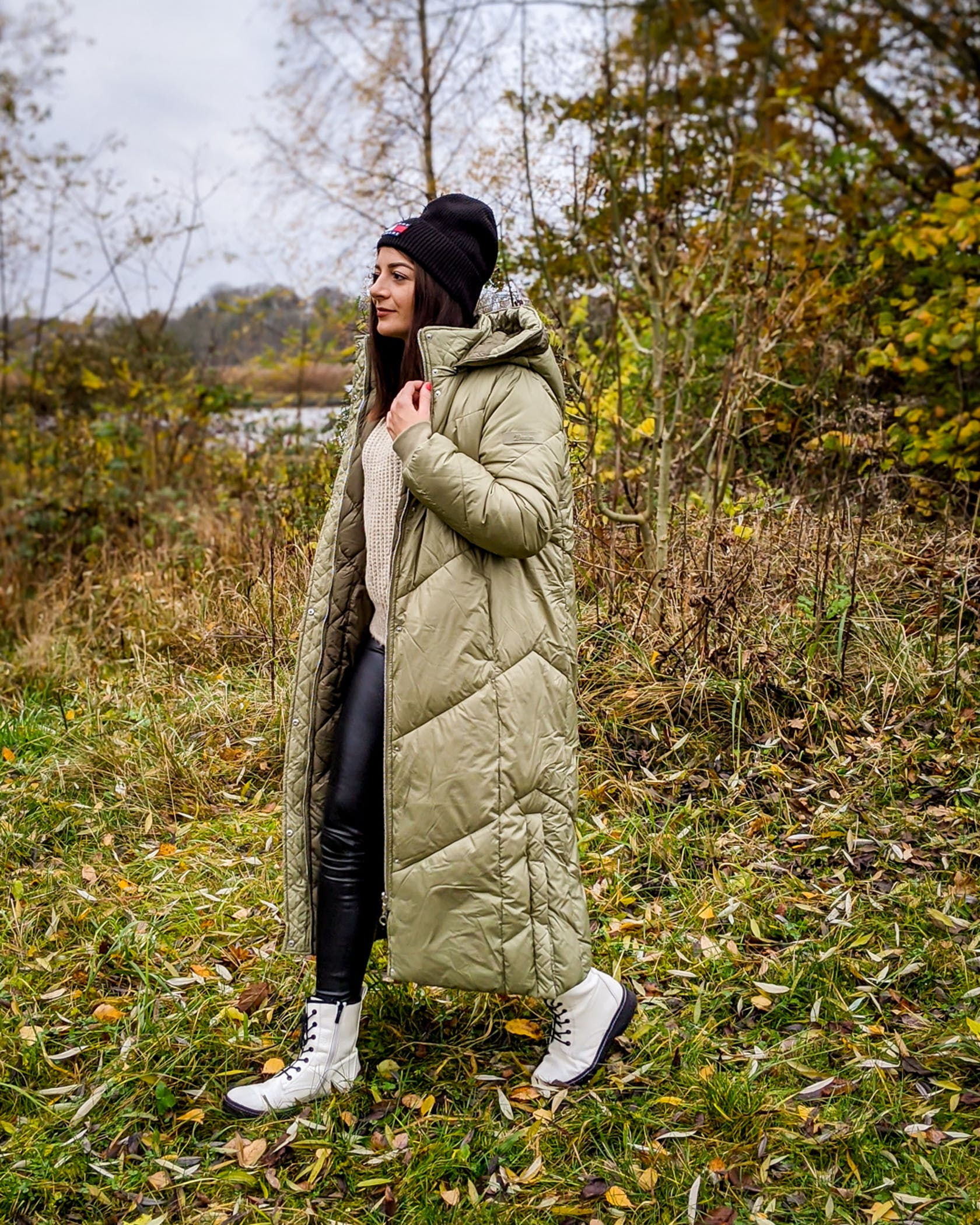 junge Frau geht in winterlichem Outfit im Wald spazieren