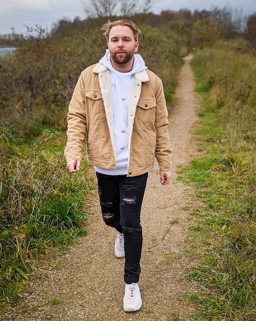 junger Mann in Outfit mit Cordjacke geht am Wasser spazieren