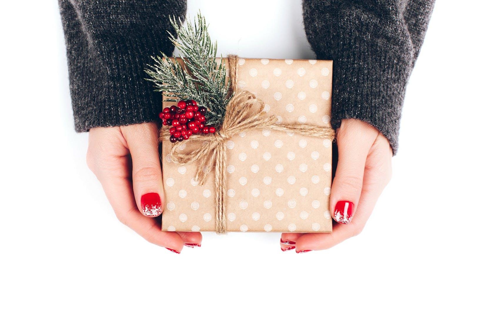 Hände in Nahaufnahme, die Geschenk halten