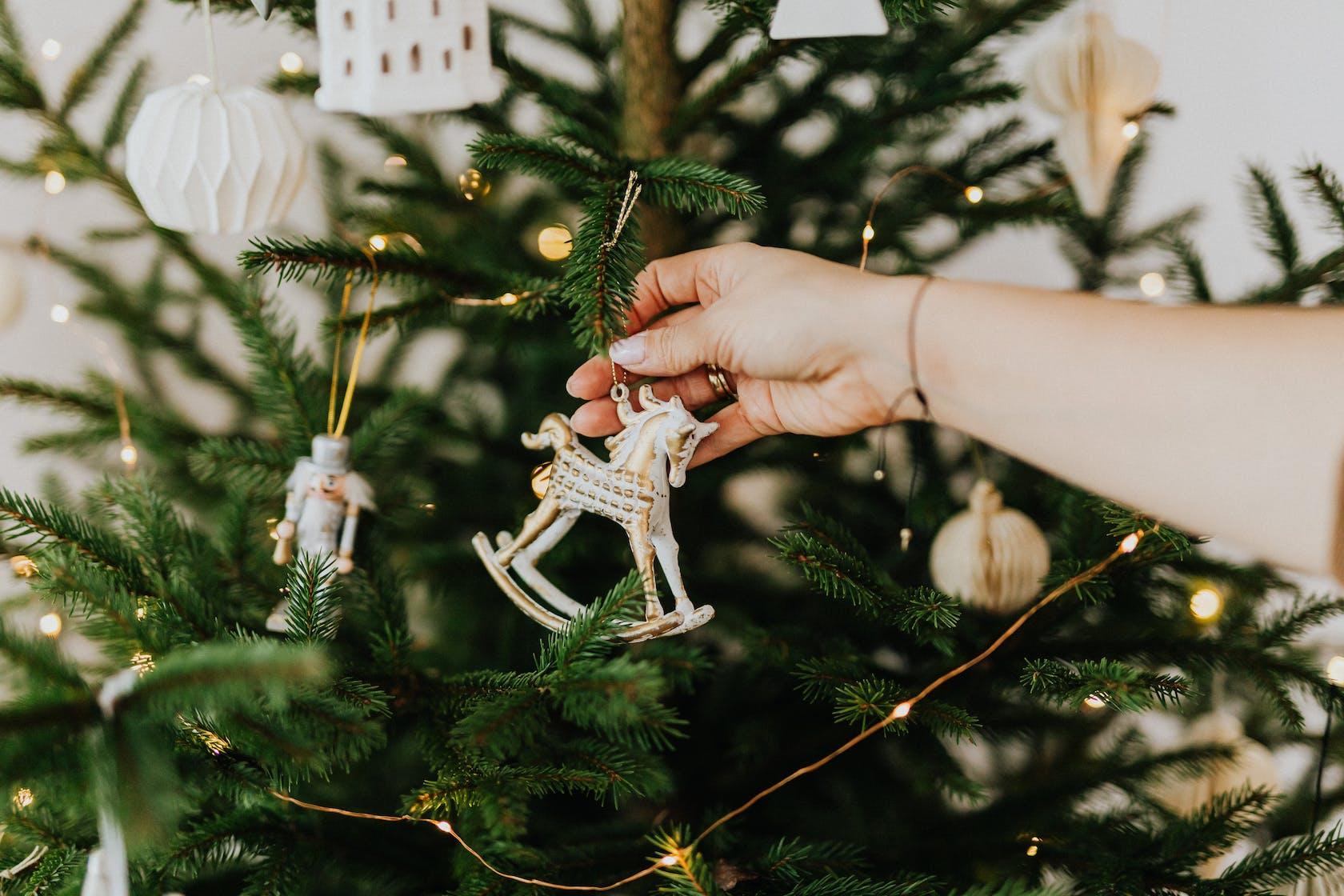 Frau hängt Weihnachtsschmuck an einen Tannenbaum
