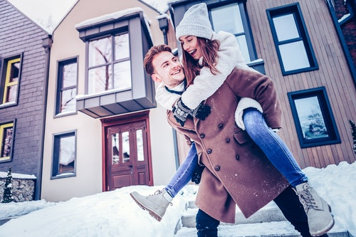 junges Pärchen geht in Winterbekleidung im Schnee spazieren