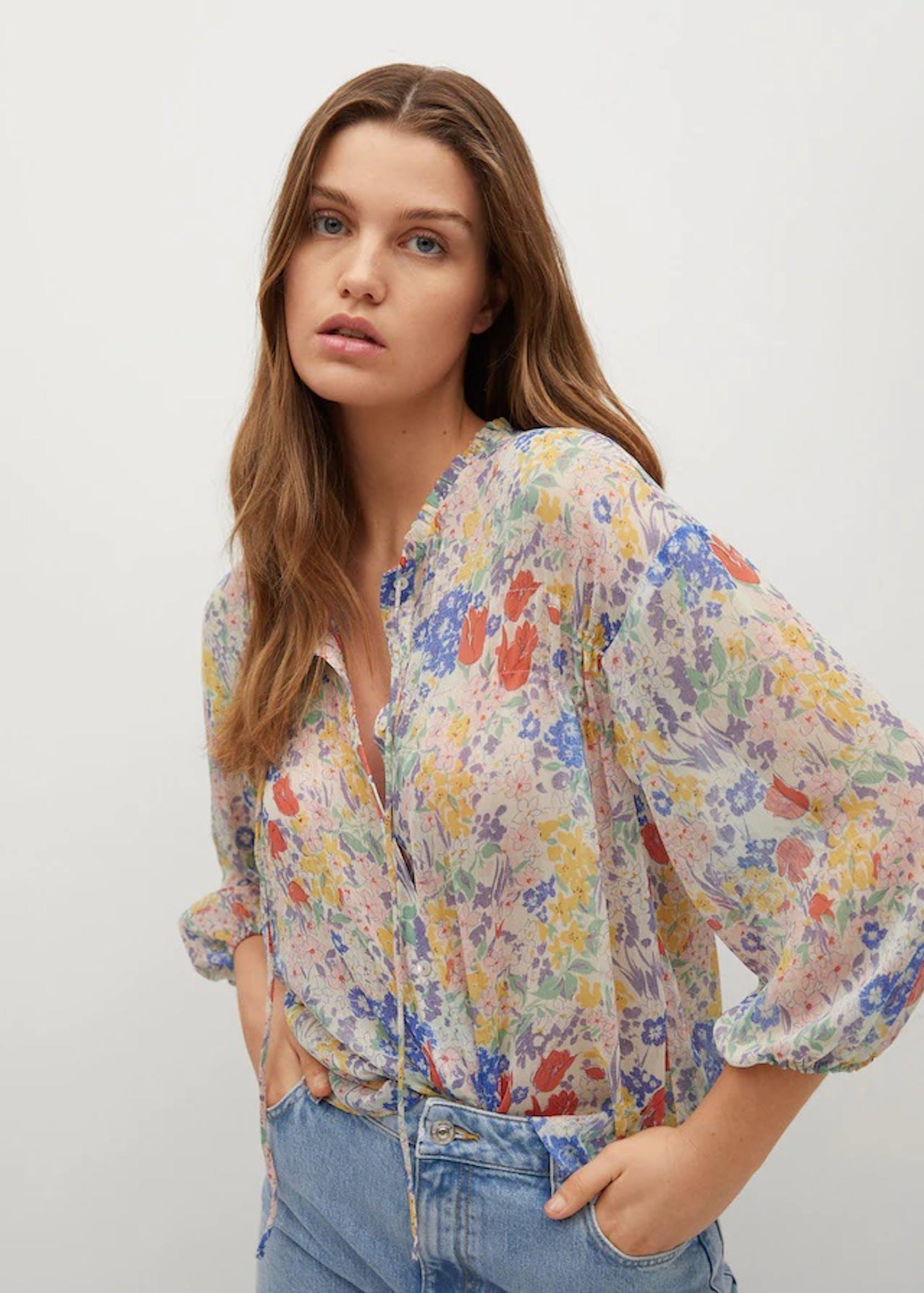 weibliches Model trägt Blumenbluse und Jeans