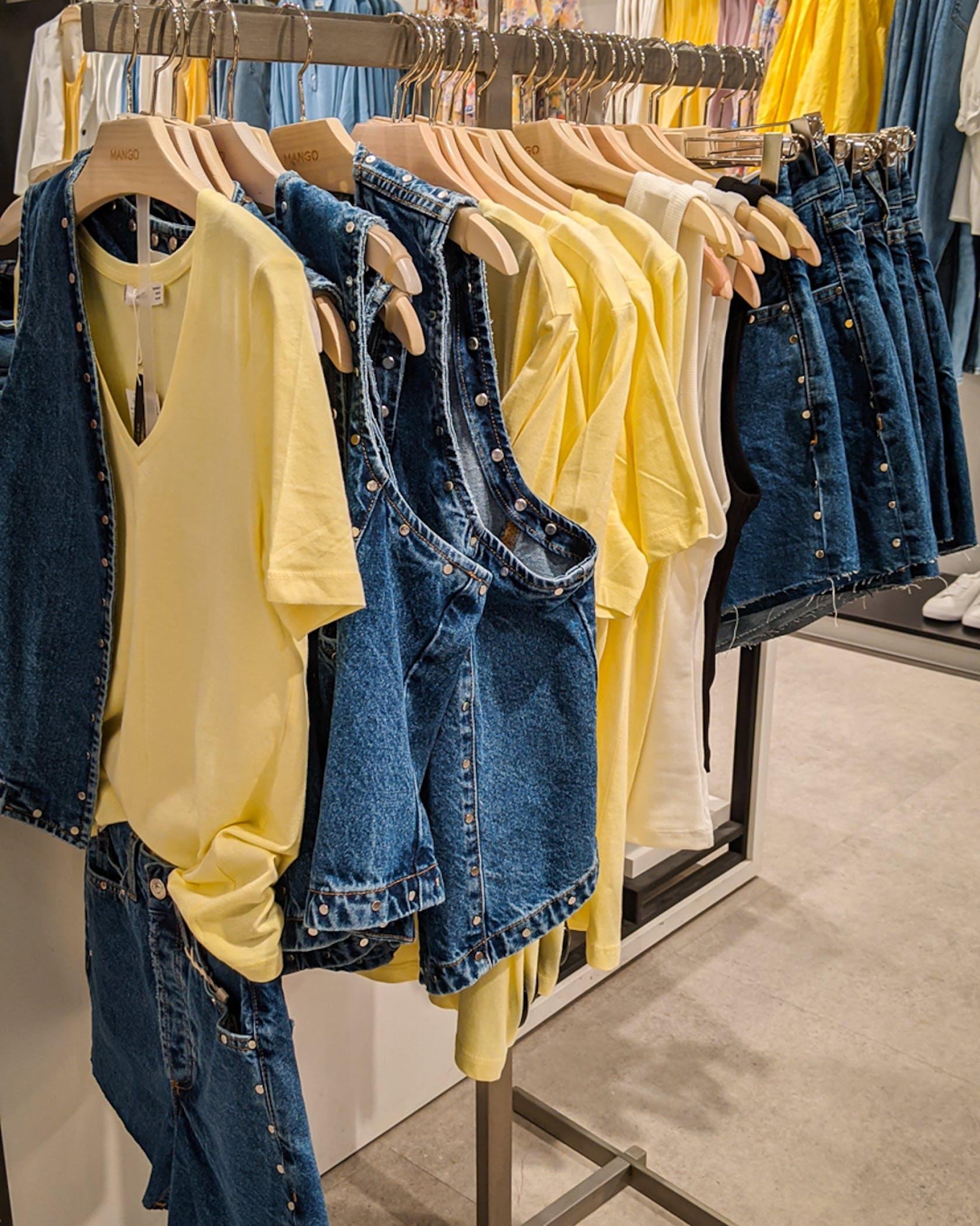 Jeanswesten, Shorts und gelbe Shirts auf einer Kleiderstange
