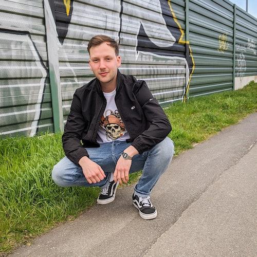 junger Mann in modischem Outfit mit Bomberjacke, Shirt und Jeans